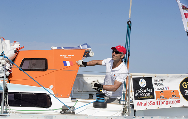 A Golden Globe Race skipper wearing a white tshirt and red hat