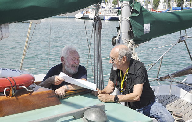Two skippers wearing black tshirts talking on a boat