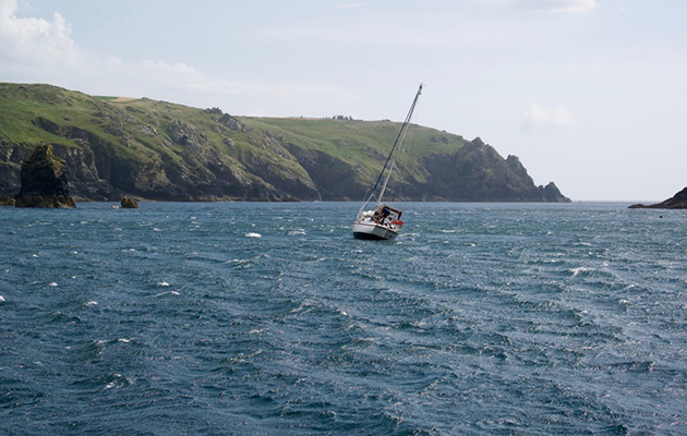 A yacht dragging its anchor in windy weather at Mullion Cove