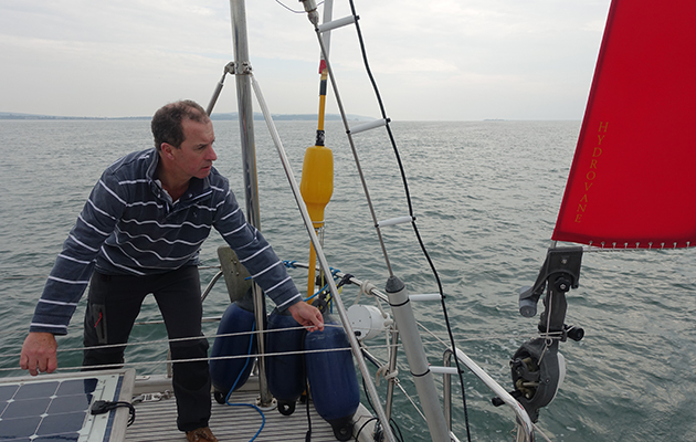 A man wearing a blue top pulls on line attached to a yacht's self steering system