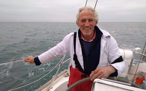 Robin Davie wearing a black top nd white jacket on board a yacht smiling