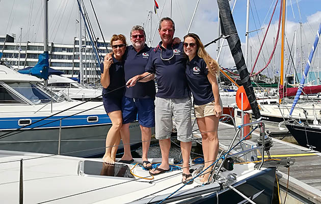 Four sailors dressed in blue t-shirts standing on the deck of a yacht