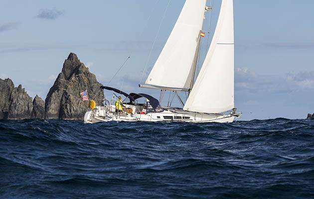 a yacht rounding a headland after crossing Biscay