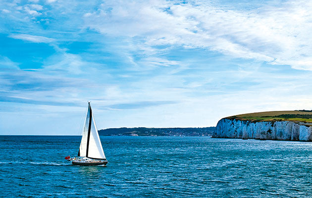 A Nordia 52 sails towards Poole past Old Harry Rocks and Swanage to the south. Photo: Gary Le Feuvre/Alamy