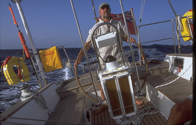 A skipper at the helm of a yacht