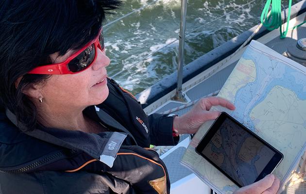 A women using digital navigation on the deck of a yacht