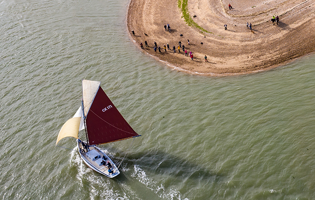 Oyster smack Peace sails past East Mersea Stone on the River Blackwater in Essex, watched by a crowd of spectators. CREDIT: Colm O'Laoi