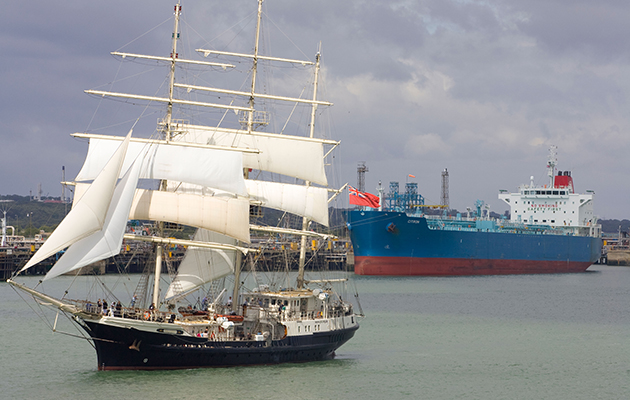 A tall ship passing a container ship