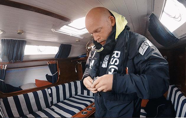 Erik Aanderaa putting on his lifejacket down below on his Contessa 35