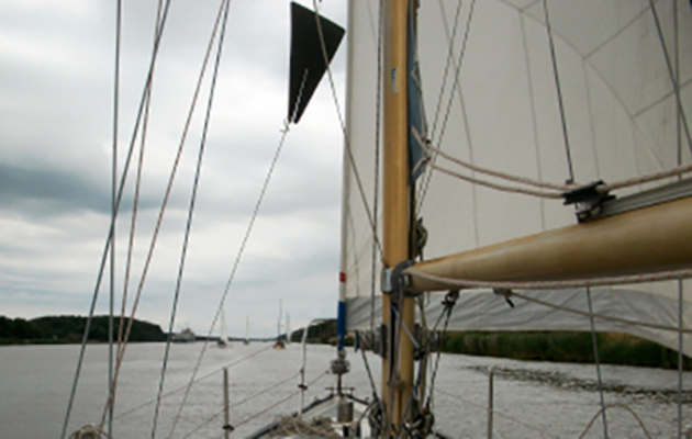 A black cone being shown while a yacht motorsails on the Kiel Canal