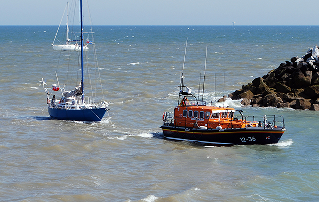 A RNLI lifeboat towing in a yacht