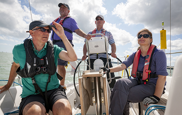 A crew sitting in a cockpit while sailing the Solent