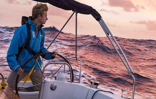 A skippers helming a yacht in the middle of the Atlantic ocean