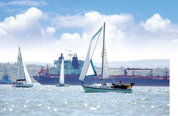 A sailing boat passes a tanker on the busy waters of the Solent off the Isle of Wight