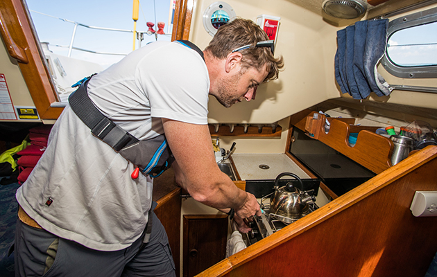 A skipper lighting a gas cooker on a boat to make a cup of tea