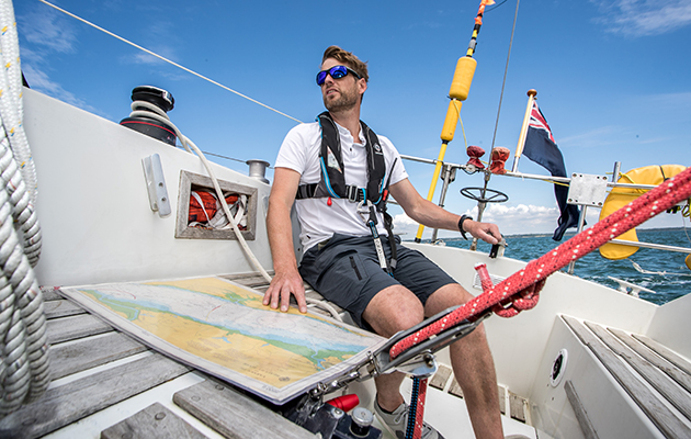A solo skipper navigating in the cockpit with a paper chart