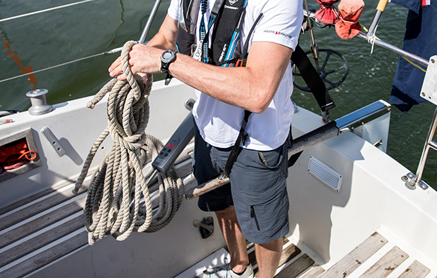 A solo skipper steering his tiller yacht with his knees