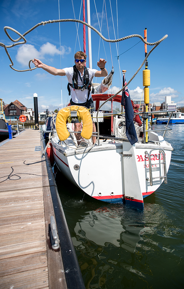 A skipper wearing a lifejacket throwing a line from a yacht