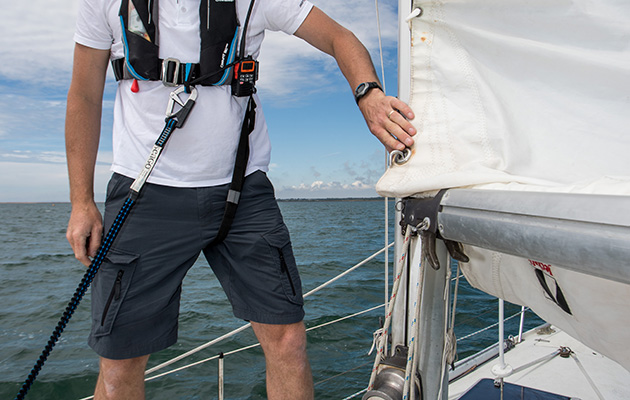 A singlehanded sail clipped on to his yacht via a harness