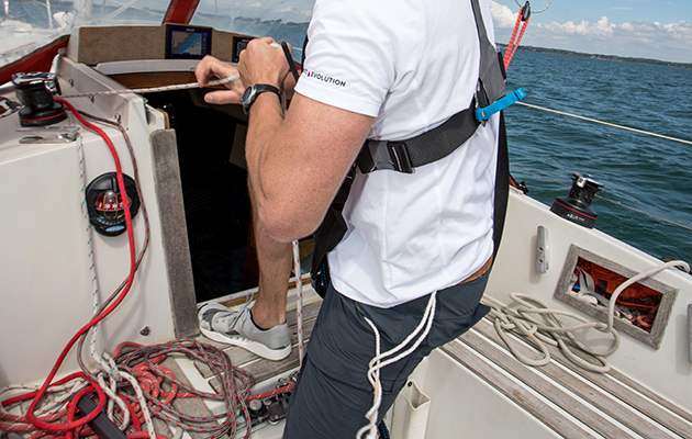 A man pulling on lines on a yacht