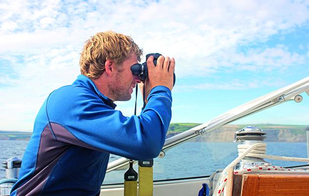 Un marin à l'aide de jumelles à bord d'un yacht