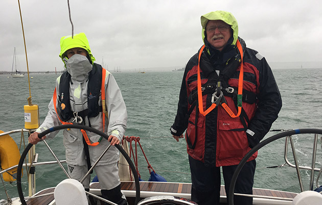 Crew on a yacht wearing waerproofs during a squall