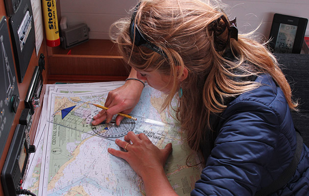 A woman plotting a course on a chart during a Day Skipper course
