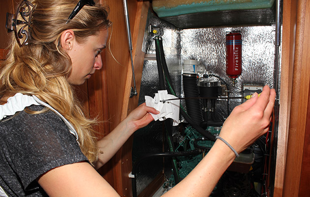 A woman checking an engine on a yacht