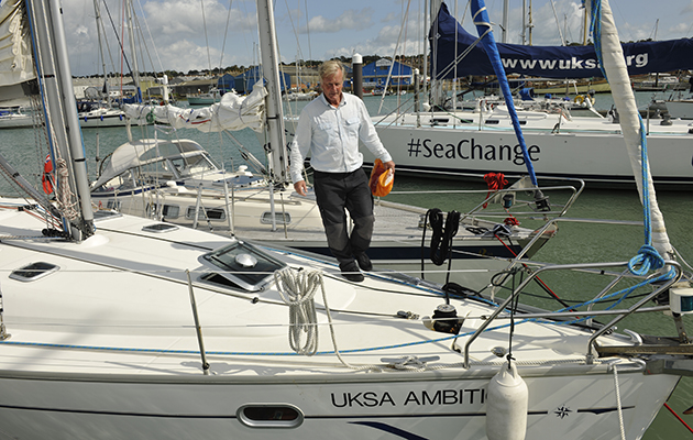 A skipper walking across the bow of a yacht