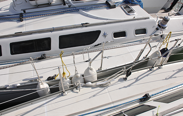 Fenders hanging off a toe rail on a yacht