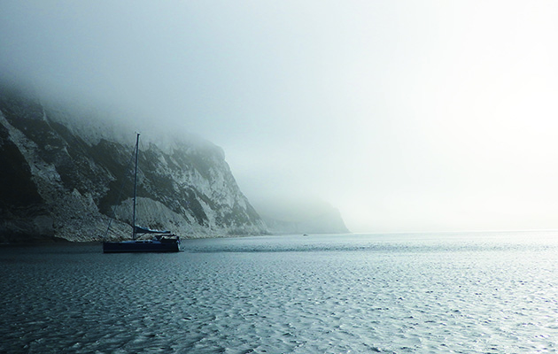 A yacht anchored in fog close to cliffs