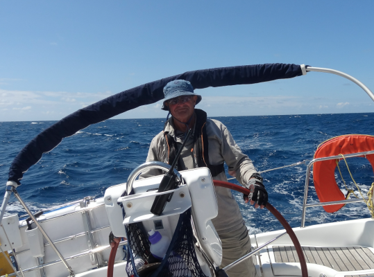 A skipper on the helm of a yacht