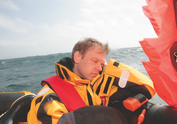 A man wearing a lifejacket in a liferaft