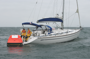 Two crew on a yacht preparing to get into a liferaft