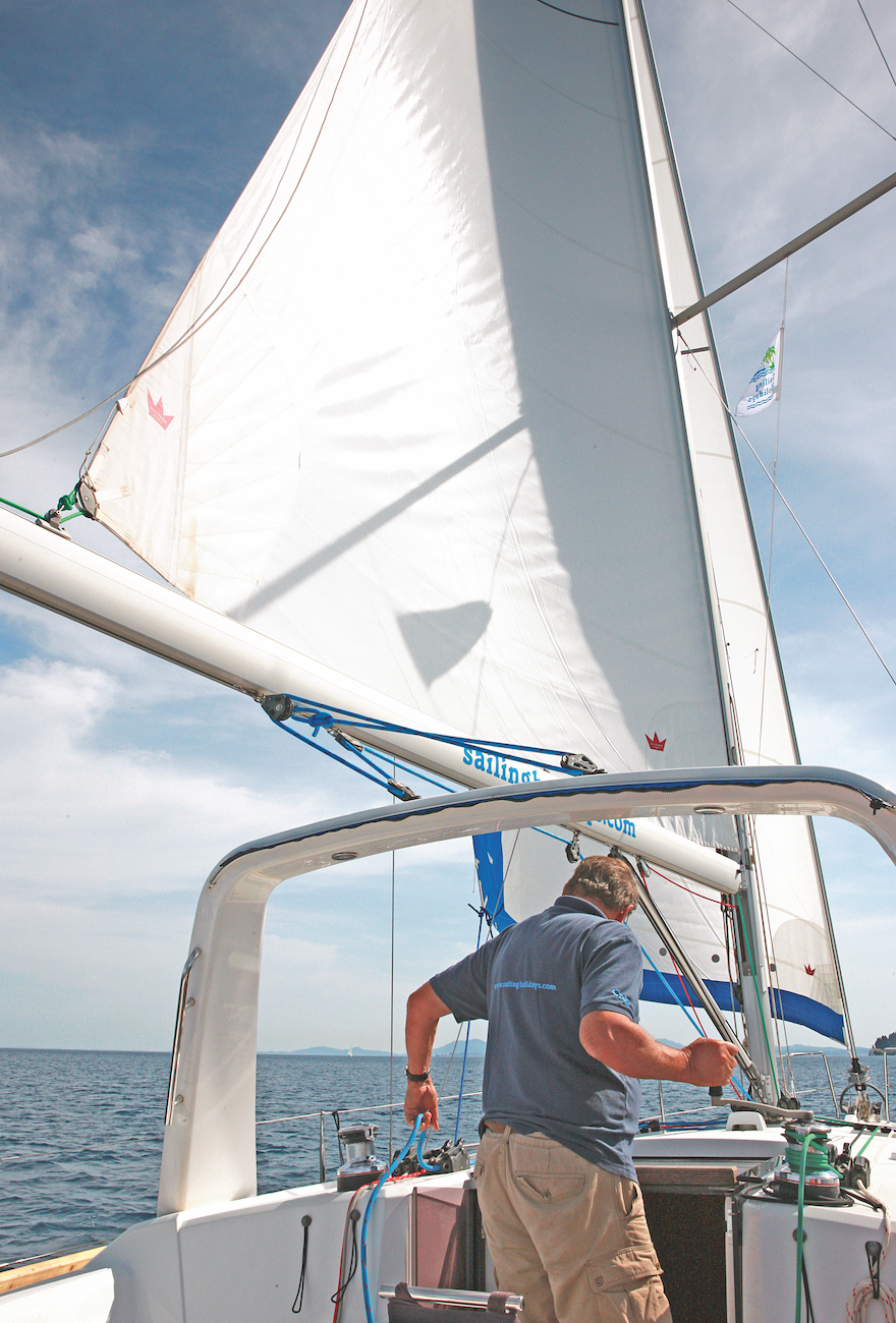A man easing a main sail via winches on a yacht