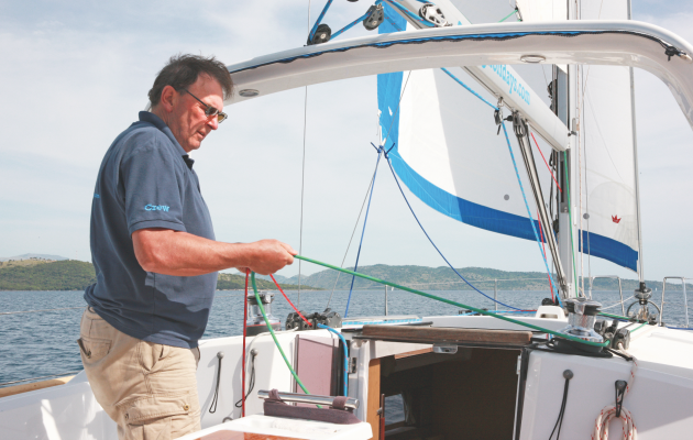 A man sorting out reefing lines on a yacht