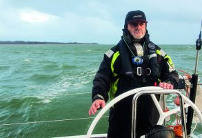 A skipper, dressed in a black cap and wet weather gear helming a yacht