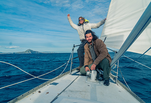 Two sailors on the deck of their yacht rounding Cape Horn