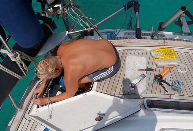 A man carrying out maintenance on his yacht