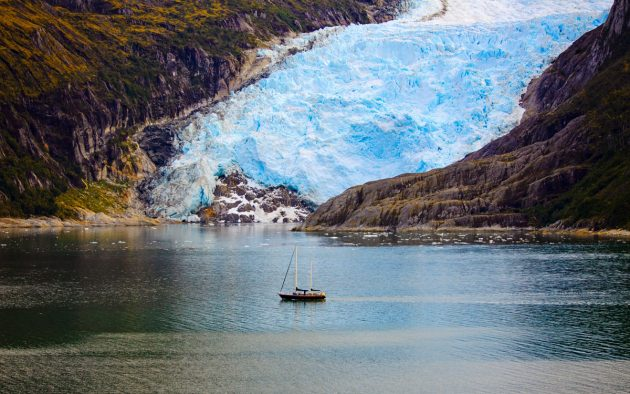 A yacht passes a glacier in the fjords of Argentina.