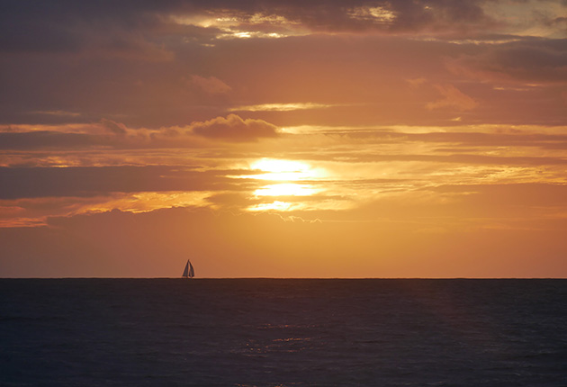 A yacht sailing over the horizon