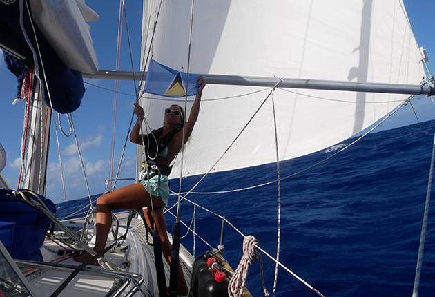 A woman raised a flag on a yacht at the end of crossing the Atlantic