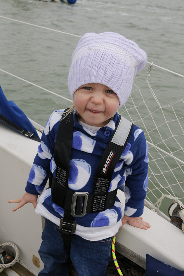 A child in a harness on a yacht