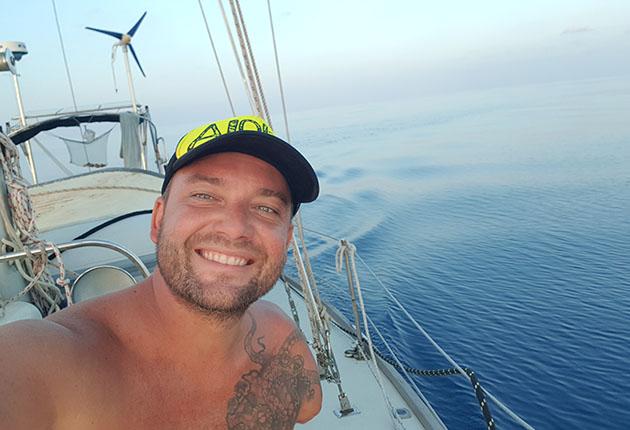 Dustin Reynolds portant une casquette sur le pont de son yacht en pleurant