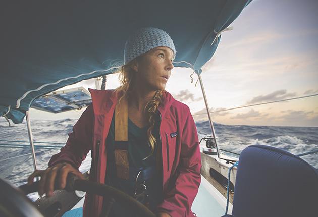 Liz Clark portant un chapeau bleu et une veste rose à la barre d'un yacht