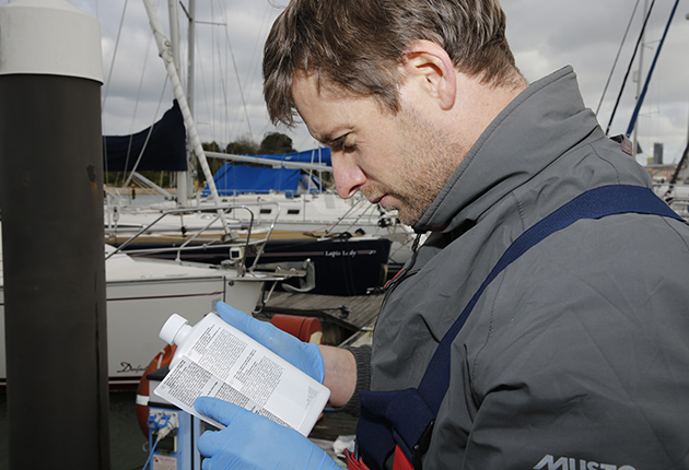 A man in a grey jacket reading the back of a bottle of canvas cleaner