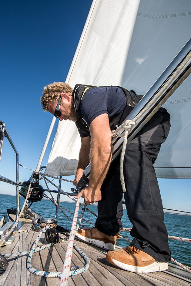 A man fixing a pole on the deck of a yacht