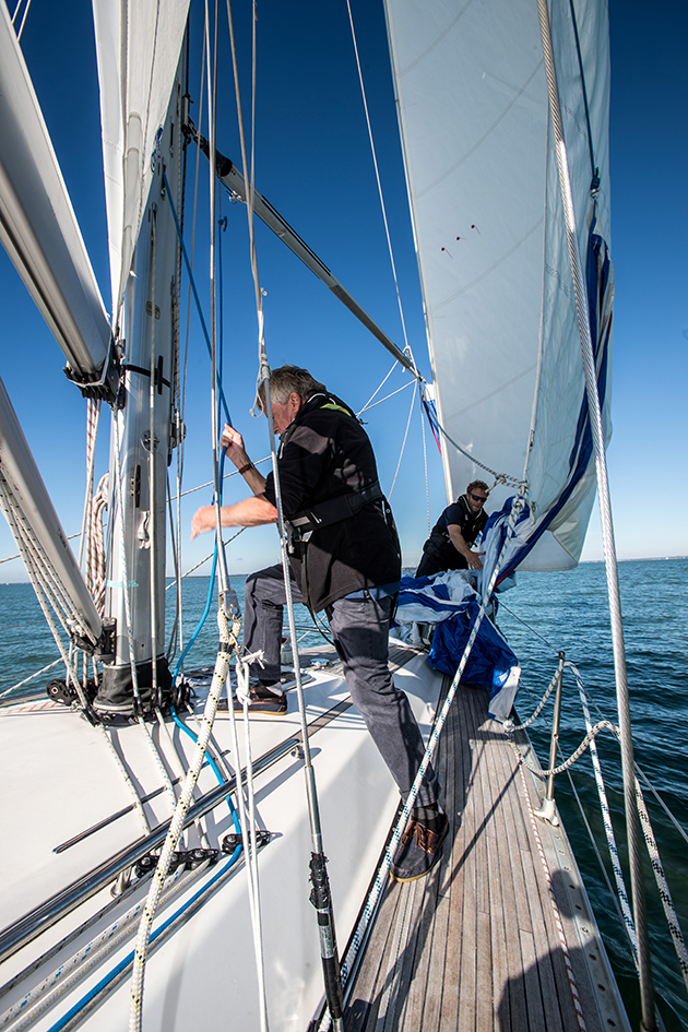 A crew pulling a line at the mast on a yacht