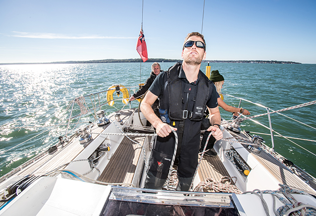 A crew member wearing sunglasses checks the spinnaker on a yacht