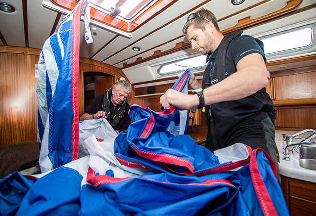 crew packing away a spinnaker on a yacht